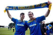 Harry Pell (L) and Jack Midson (R) of AFC Wimbledon celebrate the win that kept them in the Football League