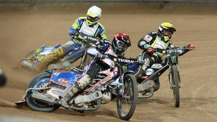 Greg Hancock (C red), in front of Krzysztof Kasprzak (L white) and Tai Woffinden (R yellow) during heat 16 of the Scandinavian FIM Speedway Grand Prix in 2014.