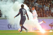 PSG's Brazilian defender Maxwell challenges Marseille's Dimitri Payet as a flare burns on the pitch