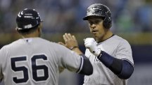 Alex Rodriguez, right, celebrates with first-base coach Tony Pena after hitting an RBI single (AP)
