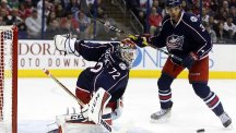 Sergei Bobrovsky (left) keeps out the the Chicago Blackhawks' Seth Jones as the Columbus Blue Jackets recorded their first win of the season (AP/Jay LaPrete)